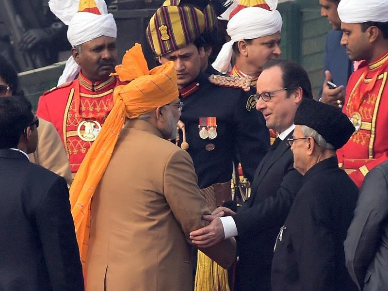 Prime Minister Narendra Modi welcomes French President Francois Hollande (C) as President Pranab Mukherjee (2R) looks on during the Republic Day Parade in New Delhi. (AFP Photo)