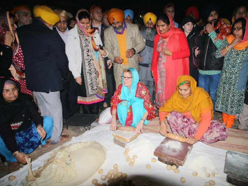 Kathleen Wynne helping in the preparation of 'guru ka langar' at Golden Temple on Sunday. (Sameer Sehgal/HT Photo)
