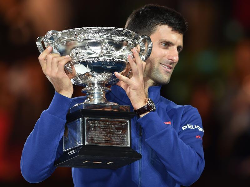 Serbia's Novak Djokovic holds up The Norman Brookes Challenge Cup after his victory during the men's singles final against Britain's Andy Murray. (AFP Photo)