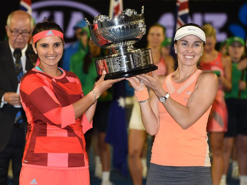 Sania Mirza and Martina Hingis pose with the trophy as they celebrate after victory in their women's doubles final match. (AFP Photo)