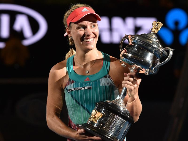 Germany's Angelique Kerber gestures as she holds The Daphne Akhurst Memorial Cup as she celebrates after victory her women's singles final match against Serena Williams. (AFP Photo)