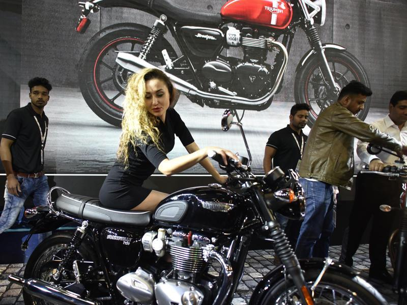 A model promotes Triumph's Bonneville T120 motorcycle at the expo. (Ravi Choudhary/ HT Photo)