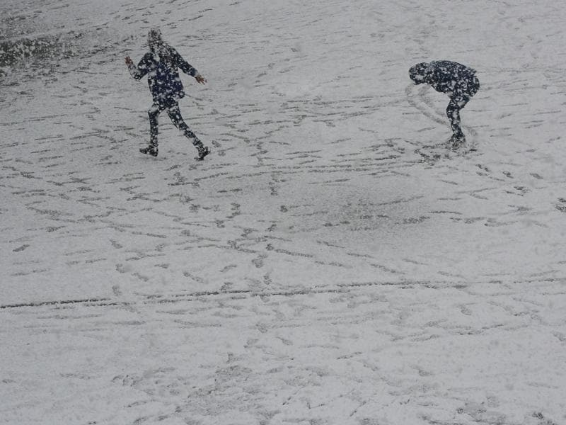 People enjoy during the first heavy snowfall at Ridge, Shimla. (Deepak Sansta / Hindustan Times)