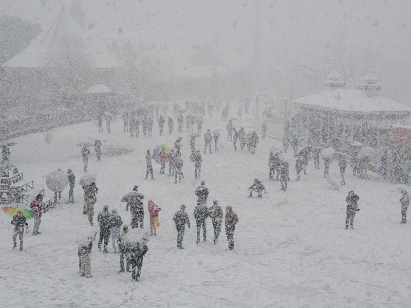 People enjoy during first heavy snowfall at Ridge, Shimla on Sunday. (Deepak Sansta / Hindustan Times)