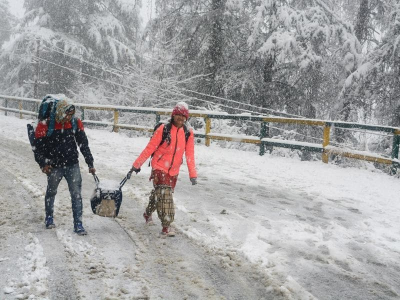 People walking with their luggage in heavy snowfall at Lakkar bazaar on Sanjauli road in Shimla . (Deepak Sansta / Hindustan Times)