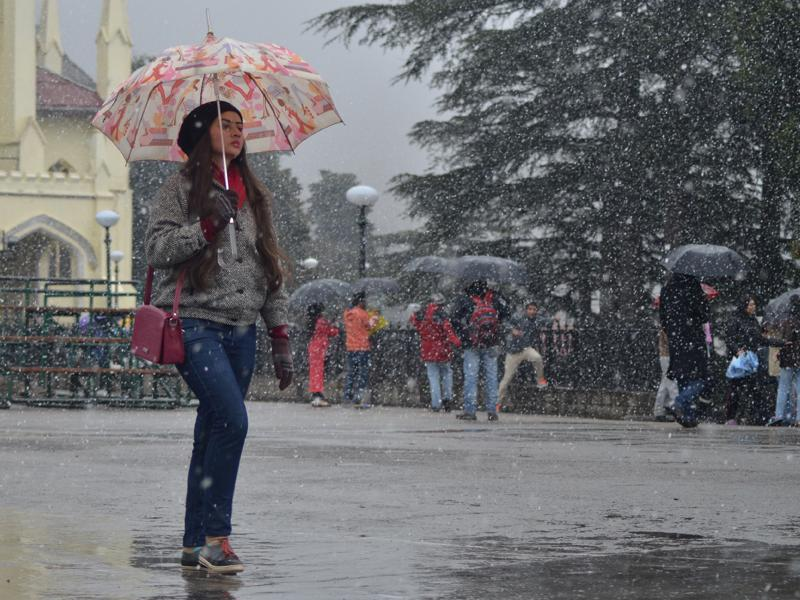 A woman walks in the snow at the Ridge in Shimla on Sunday. (photo: deepak sansta/ht)