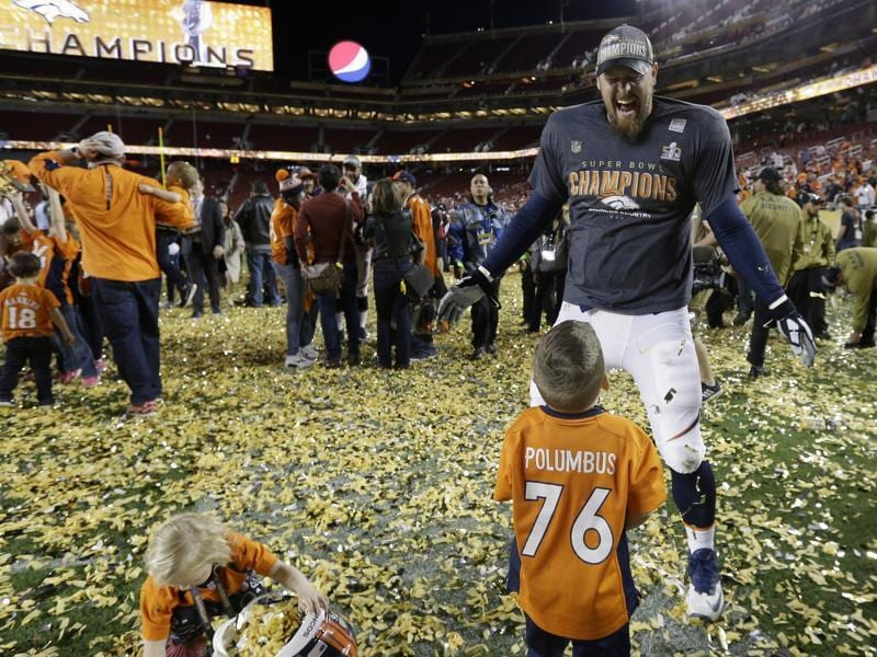 Denver Broncos' Tyler Polumbus smiles as his kids Noah and Lydia play with the confetti after the NFL Super Bowl 50 football game. (AP Photo)