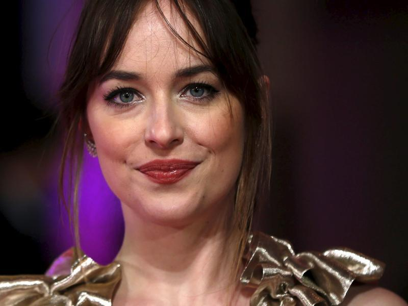 Star Dakota Johnson, famous for her role as Anastasia Steele in Fifty Shades of Grey poses for photographers at the European premiere of How to be Single. (REUTERS)