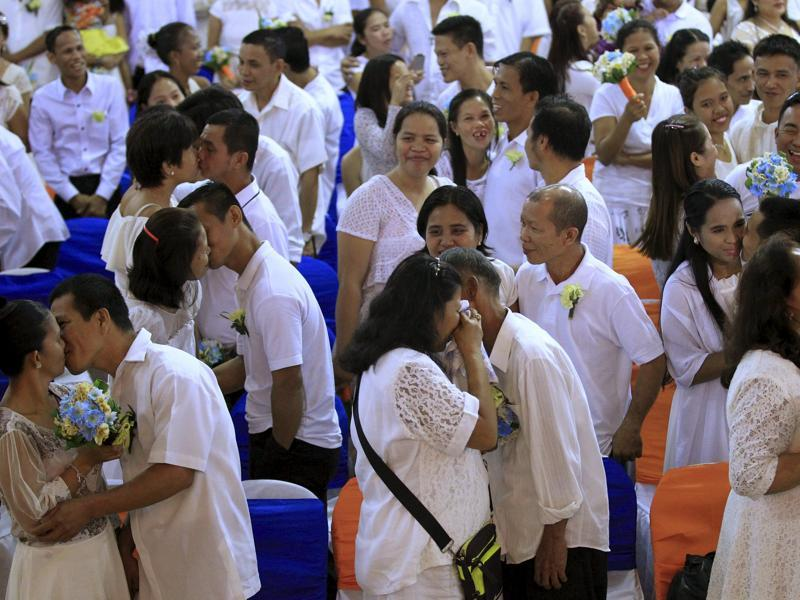 Filipino couples exchange kisses during a mass wedding ceremony ahead of Valentine's Day celebration in Manila February 12, 2016. More than 350 couples got in a mass wedding sponsored by the local government of Manila. (REUTERS)