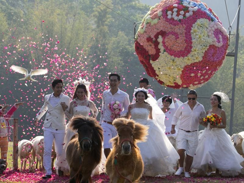 Four newlywed couples run away from a giant flower ball as a part of an adventure-themed wedding ceremony in Thailand, Saturday, Feb. 13, 2016, on the eve of Valentine's Day. (AP)
