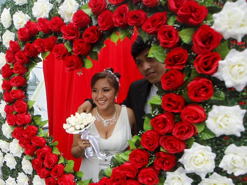 A couple poses for a picture after a mass wedding ceremony ahead of Valentine's Day celebrations in Lima, Peru, February 12, 2016. 67 couples tied the knot in a mass wedding sponsored by the mayor of Chorrillos district.  (REUTERS)