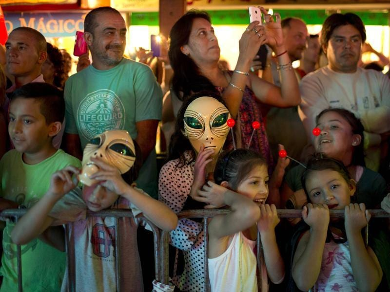 In this Feb. 13, 2016 photo, tourists watch an alien parade during the annual Alien Festival in Capilla del Monte, Cordoba, Argentina, the site of an alleged UFO sighting 30 years ago. The festival, currently hosting its fourth edition, has caused some controversy as the more fervent believers feel it has put a frivolous twist on what they consider a serious phenomenon. (AP Photo/Natacha Pisarenko) (AP)