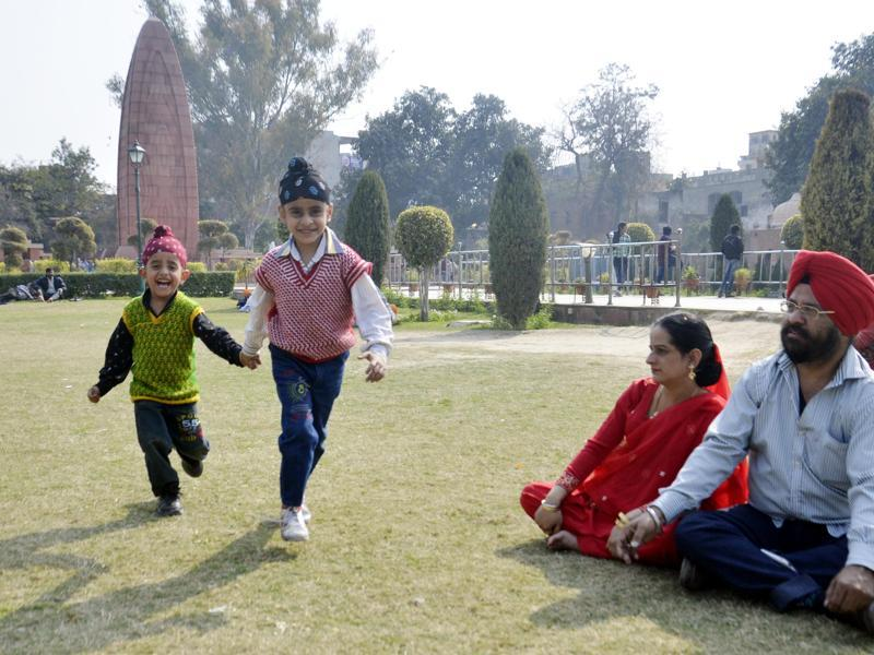 Children with parents  at Jallianwala Bagh as sun shines   in Amritsar on Thursday. (HT Photo )