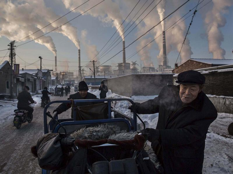 Chinese men pull a tricycle in a neighborhood next to a coal-fired power plant in Shanxi November 26, 2015. A history of heavy dependence on burning coal for energy has made China the source of nearly a third of the world's total carbon dioxide (CO2) emissions, the toxic pollutants widely cited by scientists and environmentalists as the primary cause of global warming.  (Kevin Frayer/ REUTERS)