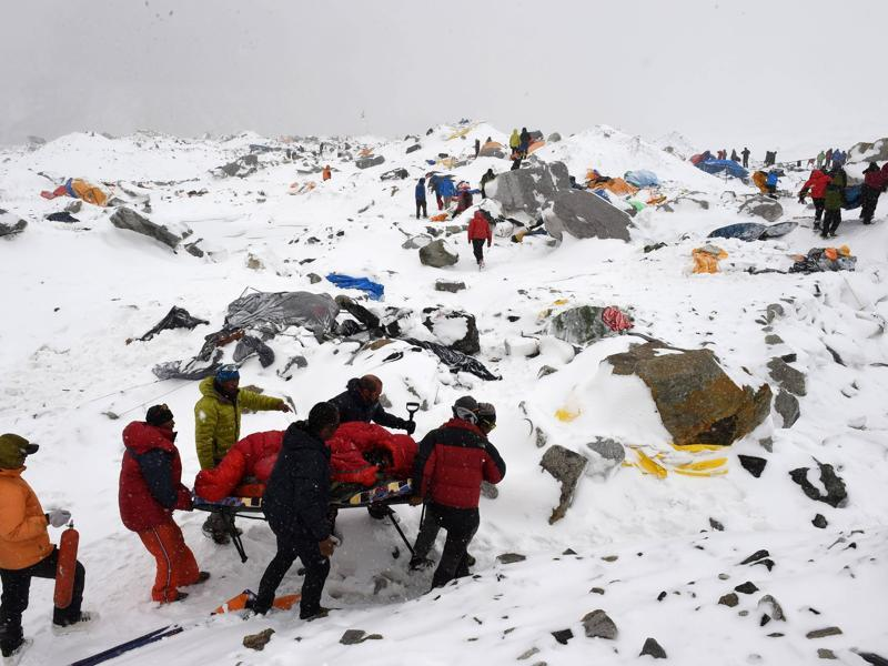 In this file photo taken by AFP photographer Roberto Schmidt on April 25, 2015 shows rescuers using a makeshift stretcher to carry an injured person after an avalanche triggered by an earthquake flattened parts of Everest Base Camp. AFP's veteran lensman Roberto Schmidt on February 18, 2016 won second prize at the prestigious World Press Photo Award in the Spot News stories category, for his dramatic shots of the deadly avalanche on Mount Everest triggered by last April's Nepal earthquake. / AFP / ROBERTO SCHMIDT (ROBERTO SCHMIDT/ AFP)