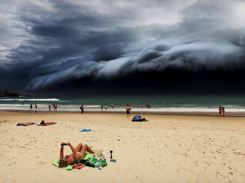 "Nature, 1st prize singles, World Press Photo Awards (Rohan Kelly - Storm Front on Bondi Beach)A sunbather is oblivious to the ominous shelf cloud approaching on Bondi beach November 6, 2015. A massive ""cloud tsunami� looms over Sydney in a spectacular weather event seen only a few times a year. The enormous shelf cloud rolled in from the sea, turning the sky almost black and bringing violent thunderstorms in its wake. REUTERS/Rohan Kelly via WPP EDITORIAL USE ONLY. NO RESALES. NO ARCHIVE (REUTERS)"