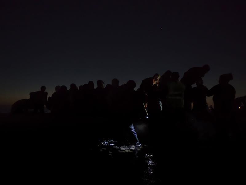 In this image released by World Press Photo titled 'Under the Cover of Darkness' by photographer Paul Hansen for Dagens Nyheter which won second prize General News singles category shows refugees traveling in darkness through Europe to avoid detection, Lesbos, Greece, Dec. 6, 2015. (Paul Hansen/ Dagens Nyheter/ AP)