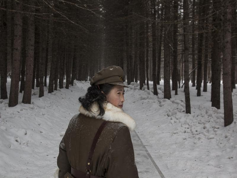In this image released by World Press Photo titled 'North Korea Life in the Cult of Kim', by photographer David Guttenfelder, AP, which won a third prize in the Long term Projects category shows a North Korean soldier, working as a guide, walking through a forest April 4, 2012, that is said to be a former camp site where the late North Korean leader Kim Il Sung overnight while leading a battle against the Japanese at the foot of Mount Paektu, North Korea.  (David Guttenfelder/ AP)