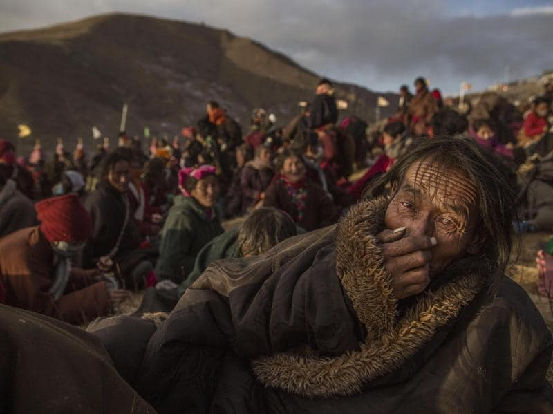 In this image released by World Press Photo titled 'Bliss Dharma Assembly' by photographer Kevin Frayer for Getty Images which won second prize in the Daily Life stories category shows Tibetan Buddhist nomads listening during the annual Bliss Dharma Assembly in Sertar county, Garze Tibetan Autonomous Prefecture, Sichuan province, China, Oct. 31, 2015. (Kevin Frayer/Getty Images, World Press Photo via AP) (Kevin Frayer/ Getty Images/ AP)