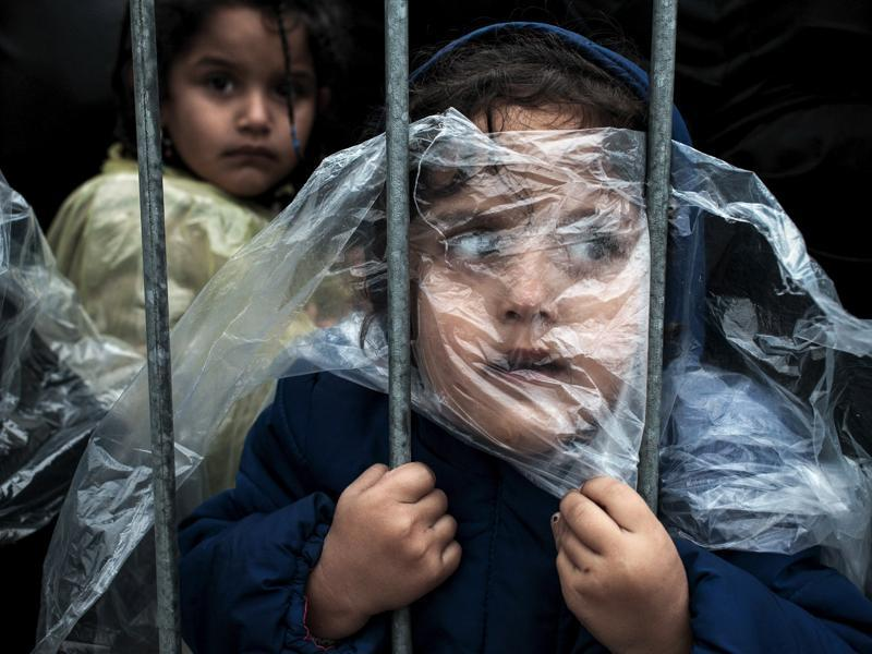 A child refugee is covered with a raincoat while she waits in line to get registered in Presevo refugee registration camp October 7, 2015. Most of the refugees who crossed Serbia try to continue their route towards Hungary, Croatia, Slovenia and other countries of the European Union. (Matic Zorman/ REUTERS)