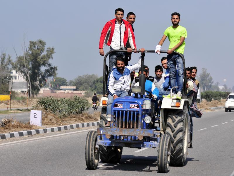 People seen riding a tractor as Jat protesters block the NH 44 near Karnal in Haryana. Over 800 trains were cancelled and with the Chandigarh-Delhi highway blocked on Sunday and airfares skyrocketing, thousands of passengers were stranded. (Ravi Kumar/HT Photo)