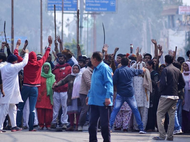 Residents gather on a street as others gesture to hold them back amid ongoing caste protests in Rohtak. Residents of the district allege that the agenda of the Jat movement has shifted from seeking reservations to indiscriminate looting and arson. (AFP)
