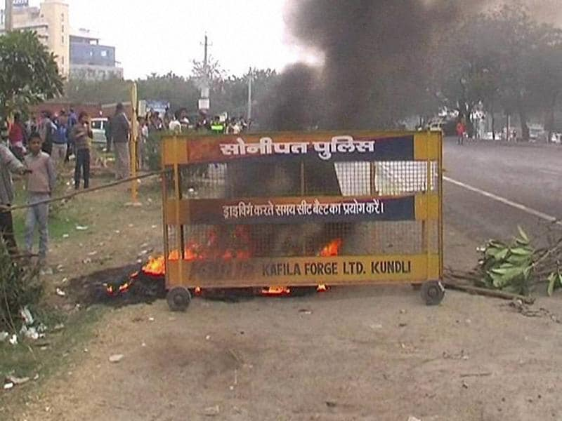 A police barricade set on fire by Jat agitators demanding reservation in Kundli, Haryana. Tensions simmered on the ground as angry mobs wielding sticks and guns set fire to shops, ATMs and looted non-Jat property (PTI)