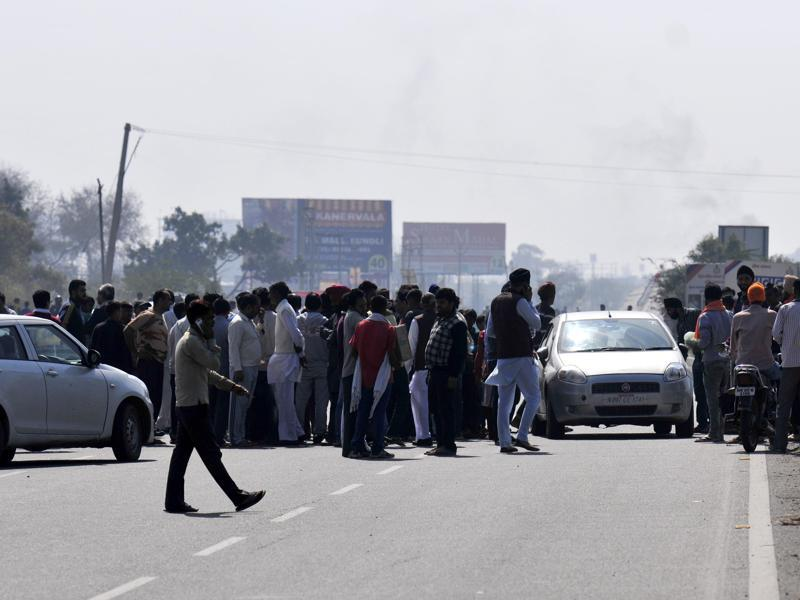 Jat supporters block the NH 44 near Karnal in Haryana. Security personnel used government vehicles to help people stranded in their houses for over a week in Rohtak town. (Ravi Kumar/HT Photo )