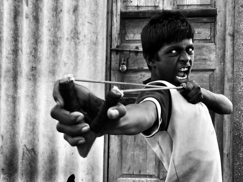 The photo, clicked in Mumbai, shows a teenager using his sling-shot to knock down a bottle after photographer Nikunj Rathod convinced a group of children to demonstrate their skills.  (Nikunj Rathod/2016 Sony World Photography Awards)