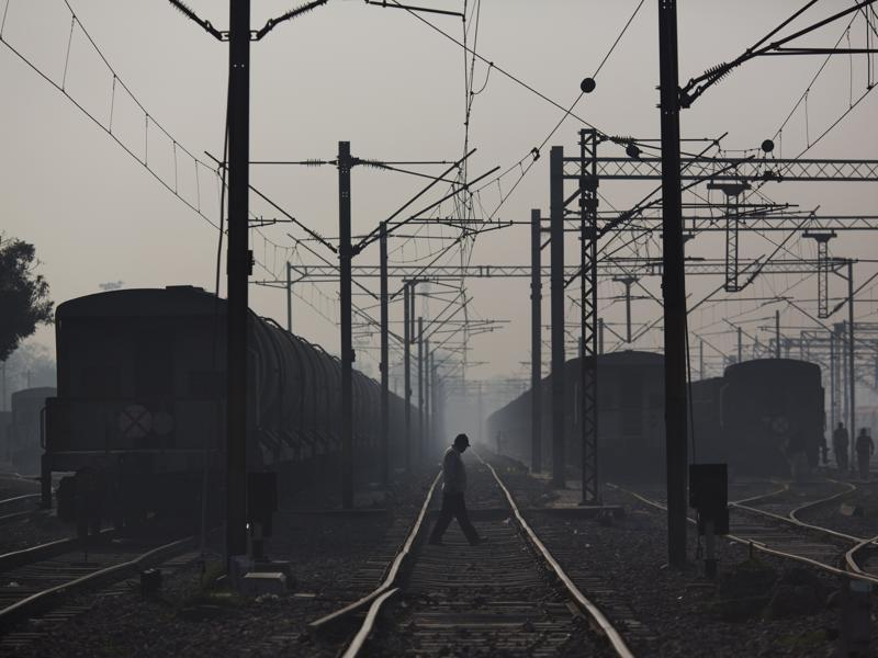 Commuters walk between rail tracks in Ghaziabad train station, on the outskirts of New Delhi. Indian Railways employs close to 1.54 million people, making it the seventh-largest employer in the world, according to Forbes. (AP Photo)