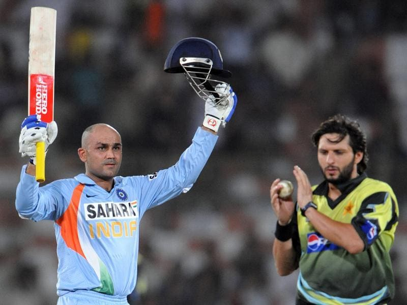 Virender Sehwag  raises his bat and helmet after he scored a century (100 runs) as Pakistani cricketer Shahid Afridi coagulates to him during  match between Pakistan and India at the National Cricket Stadium in Karachi. (AFP Photo)