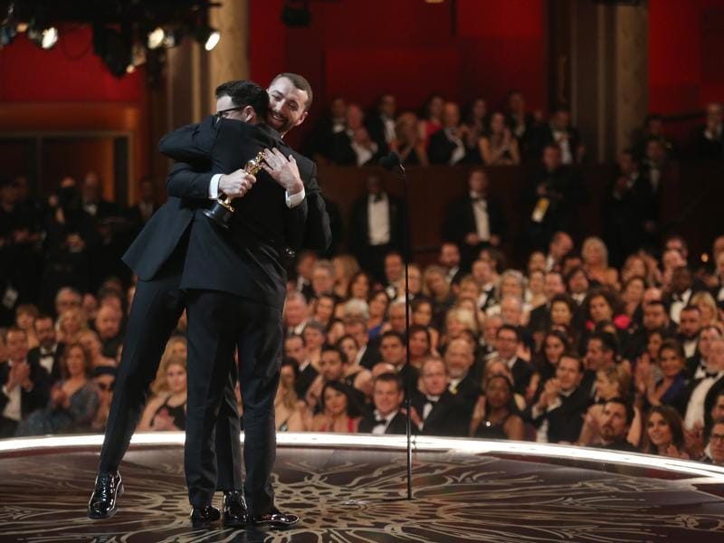 Jimmy Napes, left, and Sam Smith as seen from backstage as they hug it out after accepting the award for best original song for Writing's On The Wall for Spectre at the Oscars. (AP)