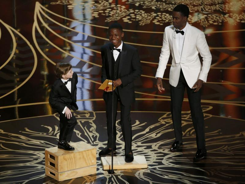 Host Chris Rock brings out apple boxes for young presenters Jacob Tremblay and Abraham Attah to reach the microphone at the 88th Academy Awards in Hollywood. (REUTERS)