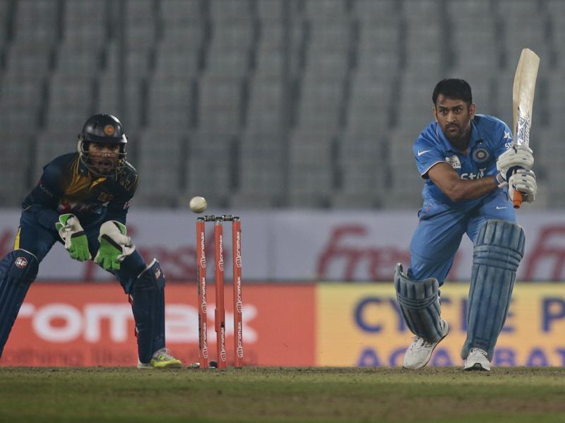 India's captain Mahendra Dhoni, right, plays a shot, as Sri Lanka's wicketkeeper Dinesh Chandimal follows the ball during their Asia Cup Twenty20 international cricket match. (AP Photo)