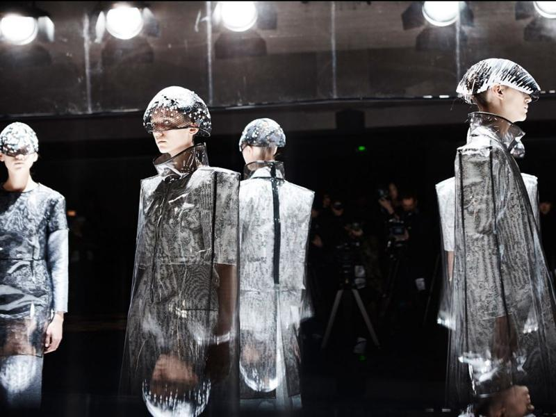 "Anrealage: Last season, this label's clothes revealed hidden color when flashed by cameras and smartphones. For autumn/winter 2016, Anrealage is back with another futuristic, technology-inspired collection themed around ""Noise."" The collection used various shades of gray, sometimes revealing stripes and checks. (March 1, 2016). (AFP)"