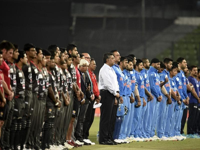 United Arab Emirates and India cricketers stand in a moment of silence for former New Zealand captain Martin Crowe. (AFP Photo)