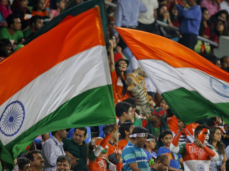 Indian spectators wave their national flags. (AP Photo)