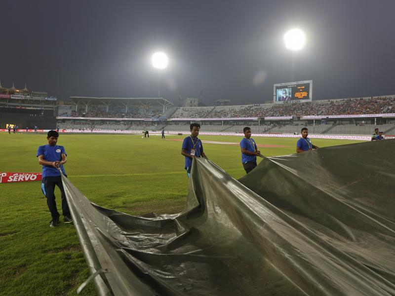 Bangladeshi ground staff pull covers on the field as it rains ahead of the Asia Cup Twenty20 international cricket final match. (AP Photo)