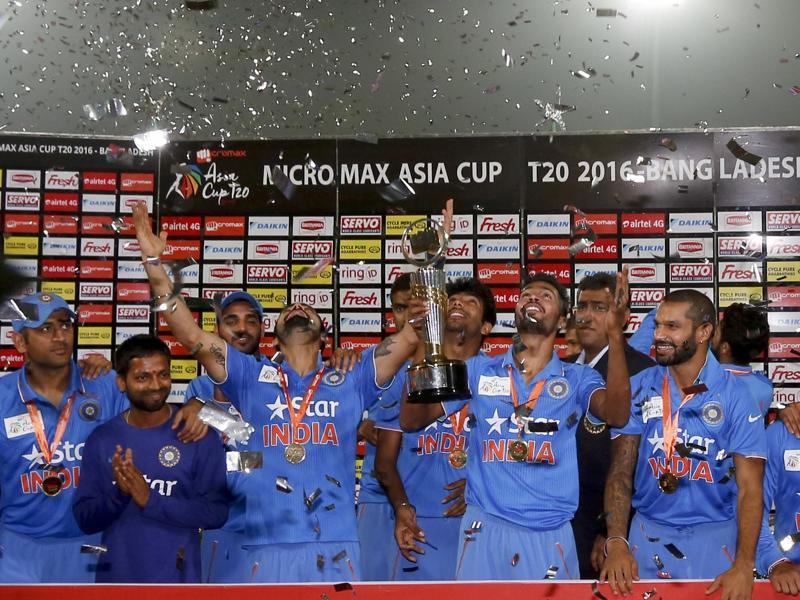 A victorious Team India pose with the Asia Cup trophy as confetti is showered on them during the presentation ceremony. (AP Photo)