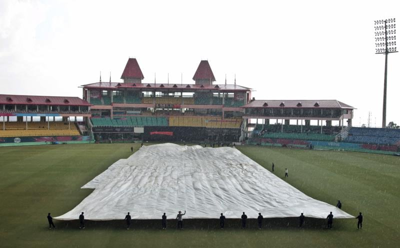 Ground staff at the Himachal Pradesh Cricket Association (HPCA) stadium in Dharmsala cover the pitch with tarpaulin during a sudden hailstorm in Dharmsala. (AP Photo)