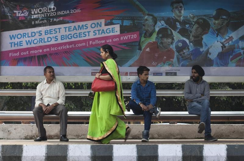 Commuters wait under a banner of ICC world Twenty20 tournament at a bus stand in New Delhi. (AP Photo)