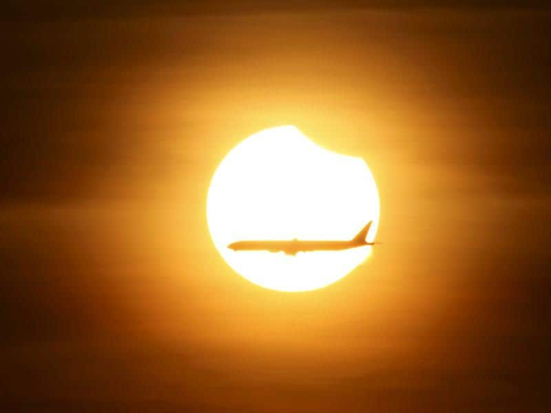 An aeroplane flies past the sun as it goes into a partial solar eclipse in Singapore on Wednesday. (Reuters)