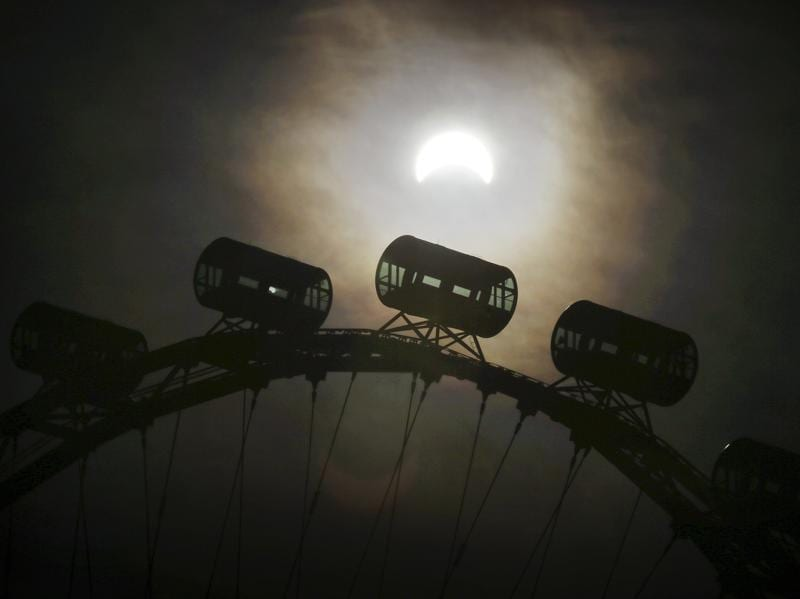 A partial solar eclipse is seen behind passenger capsules of the Singapore Flyer on Wednesday morning. The last eclipse Singapore witnessed was in January 2009 and the next solar eclipse, an annular one, will occur on December 26, 2019. (AP)