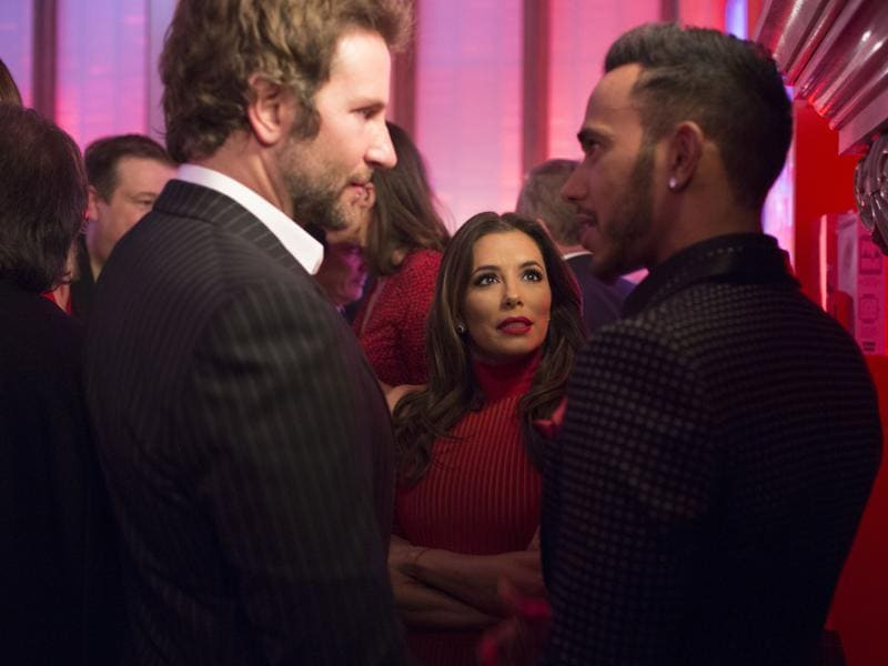 Actors Bradley Cooper and Eva Longoria in conversation with British Formula One racing superstar Lewis Hamilton. (NYT)