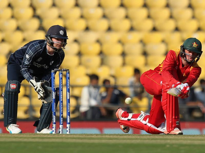 Sean Williams  of Zimbabwe plays a shot as Scotland's Matt Cross looks on. (AFP Photo)