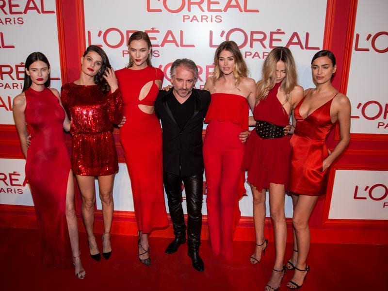 Stunners in red: Cyril Chapuy (centre) poses with a bevy of beauties.  (AP)