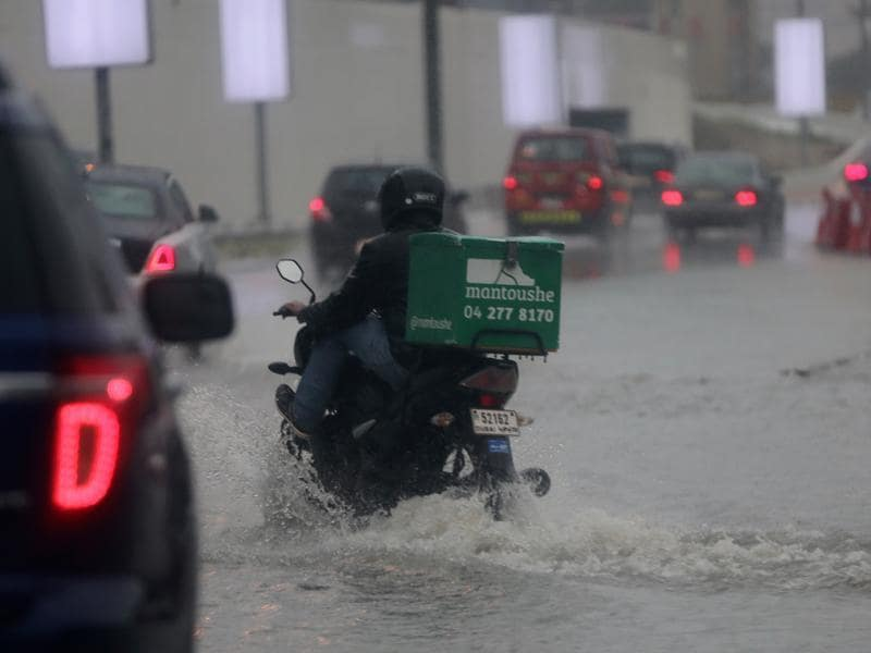 A delivery man rides his bike during heavy rain in Dubai. (AP)
