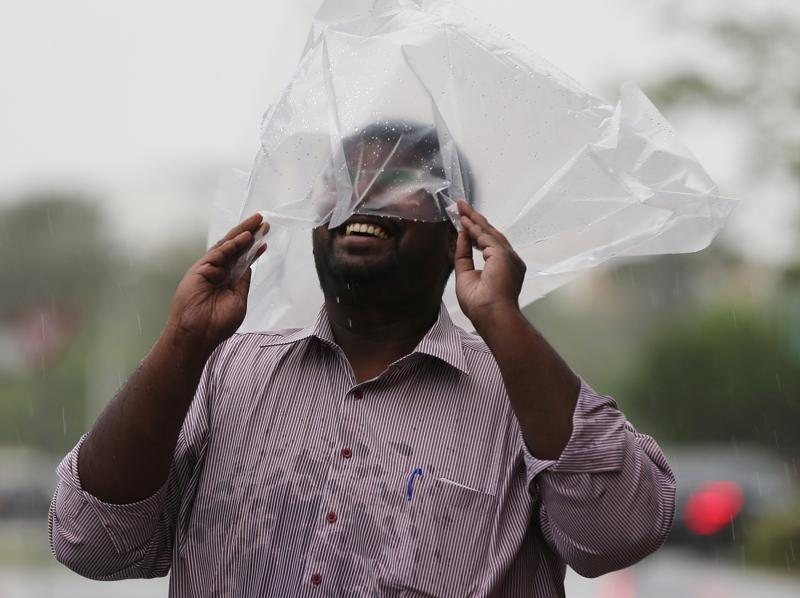 A man covering his head with a plastic bag enjoys walking in the rain in Dubai, United Arab Emirates. (AP)