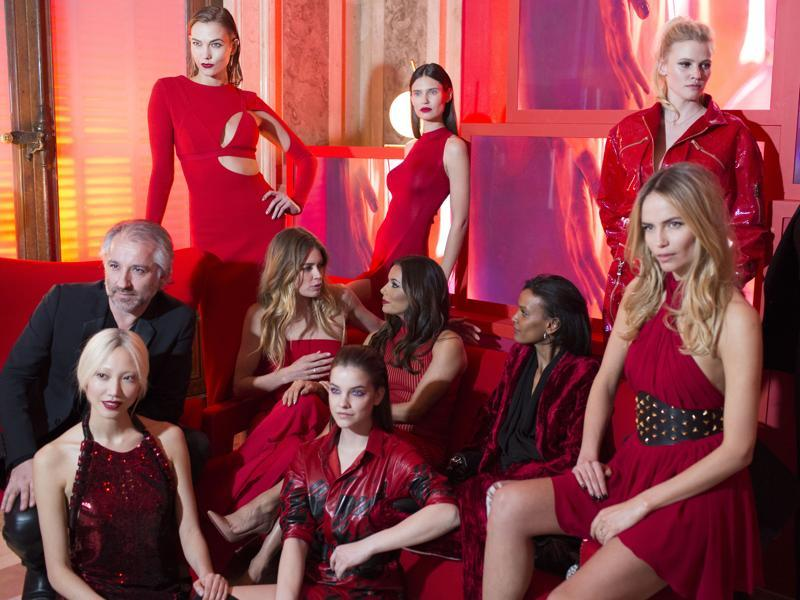 Sizzling in red: Models at the L'Oreal Red Obsession party pose for photographers in Paris, March 8, 2016. The end of Paris Fashion Week is always an occasion for A-list parties. Also seen is Cyril Chapuy (left), president, L'Oreal. (NYT)