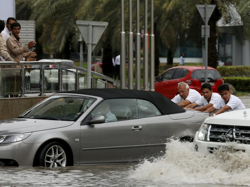 People push a car through flood waters during a rain storm in Dubai. (REUTERS)